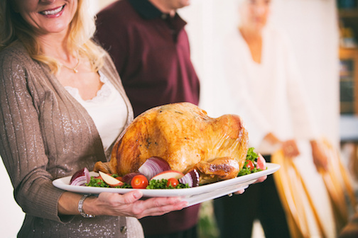 Traditional Thanksgiving holiday in the USA, with family preparing turkey and gathering around the table.