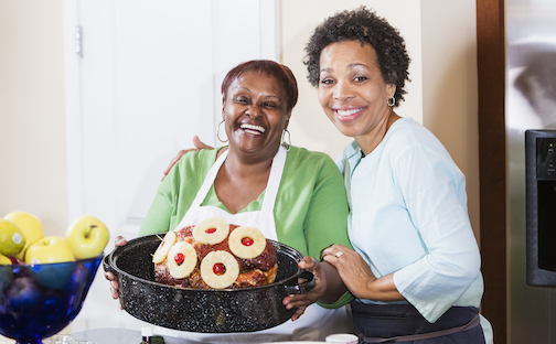 Women in kitchen cooking Easter Ham for family celebration