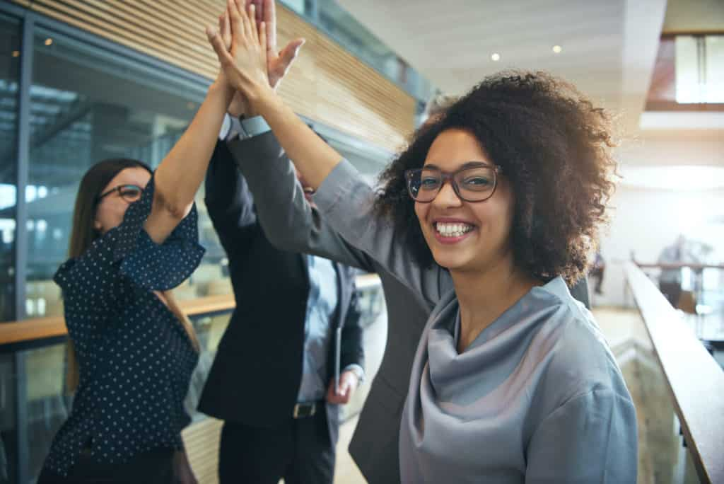 Coworkers high-five kicking off a year of workplace kindness and gratitude